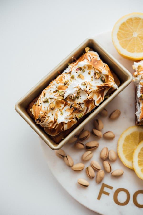 Вертикальная надземная съемка вкусного десерта торта с гайками и лимонами на белых плите и предпосылке стоковые изображения rf