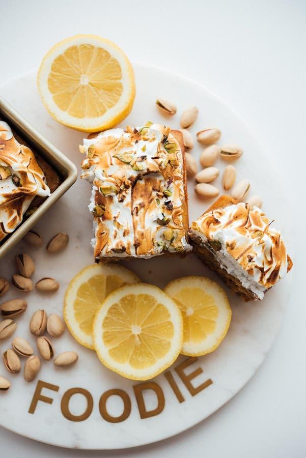 Вертикальная надземная съемка вкусного десерта торта с гайками и лимонами на белых плите и предпосылке стоковое изображение rf