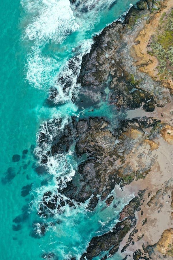 Вертикальная надземная съемка красивого бечевника моря с голубыми чистой водой и песчаным пляжем стоковые фото