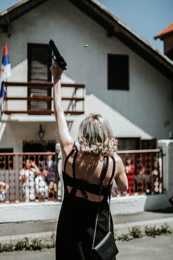 Вертикальная съемка задней части белокурой женщины в мини платье держа пистолет и снимая его вверх стоковая фотография