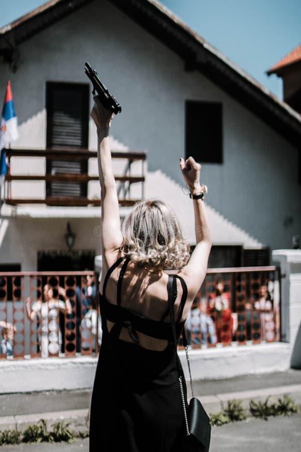 Вертикальная съемка задней части белокурой женщины в мини платье держа пистолет и снимая его вверх стоковая фотография rf