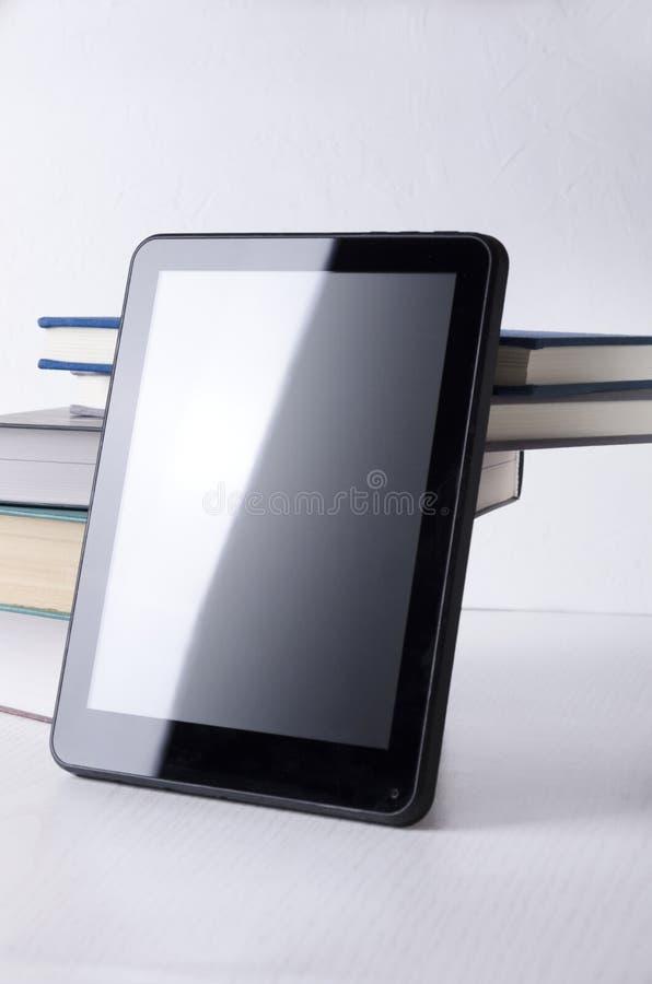 Вертикальная съемка планшета против кучи книг E-образование, e-чтение, обучение по Интернету стоковая фотография