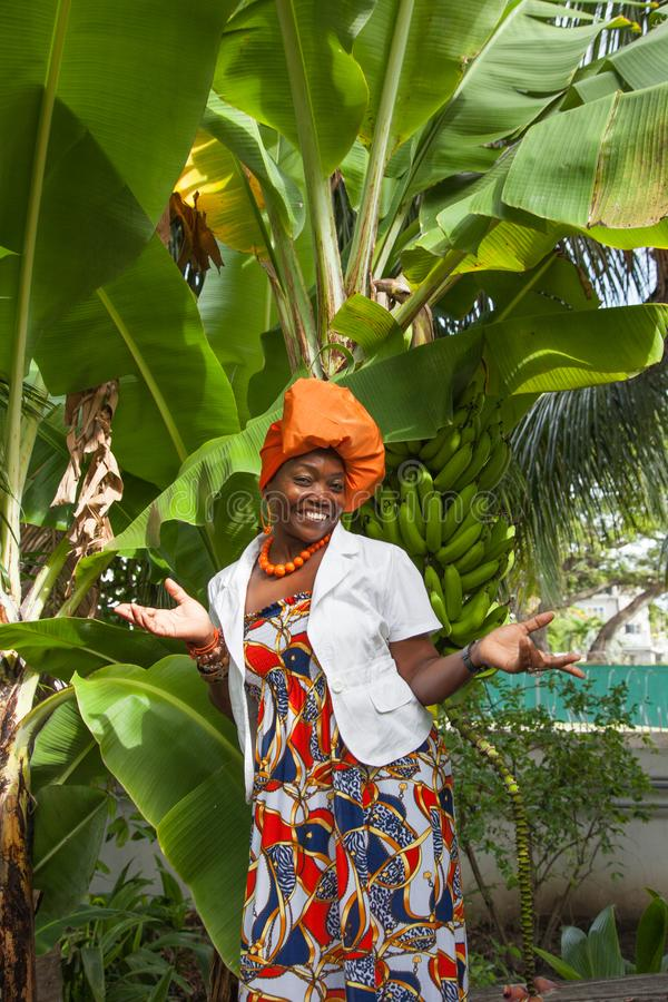 Вертикальное полное тело радостной Афро-американской женщины нося представления яркие красочные национальные платья стоковое фото rf