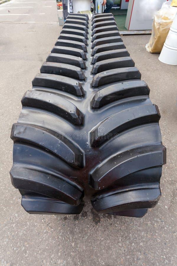 Вертикальное фото используемой черной резиновой гусеницы на асфальте стоковые изображения
