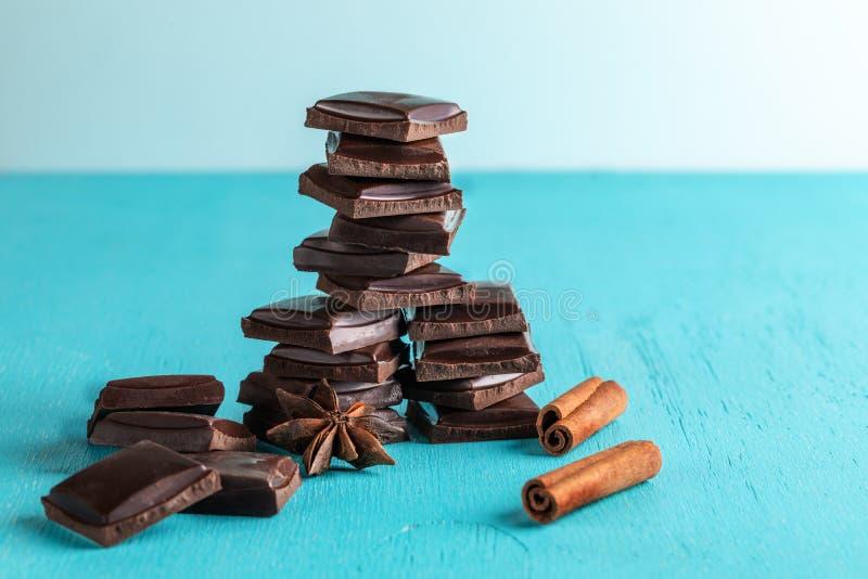 Вертикальные штабелированные куски шоколада, ручки циннамона и анисовки звезды на предпосылке бирюзы стоковые фотографии rf