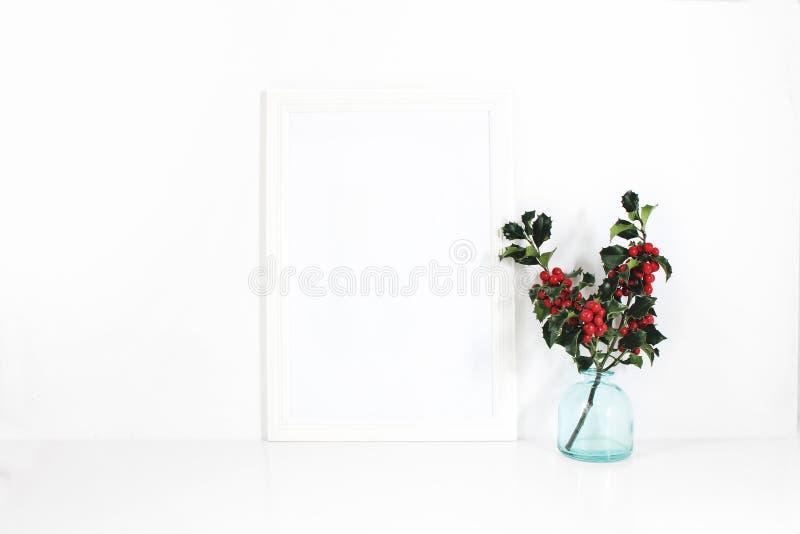 Вертикальный белый пустой модель-макет деревянной рамки Ветви ягоды падуба в вазе синего стекла на белой таблице Введенный в моду стоковые изображения