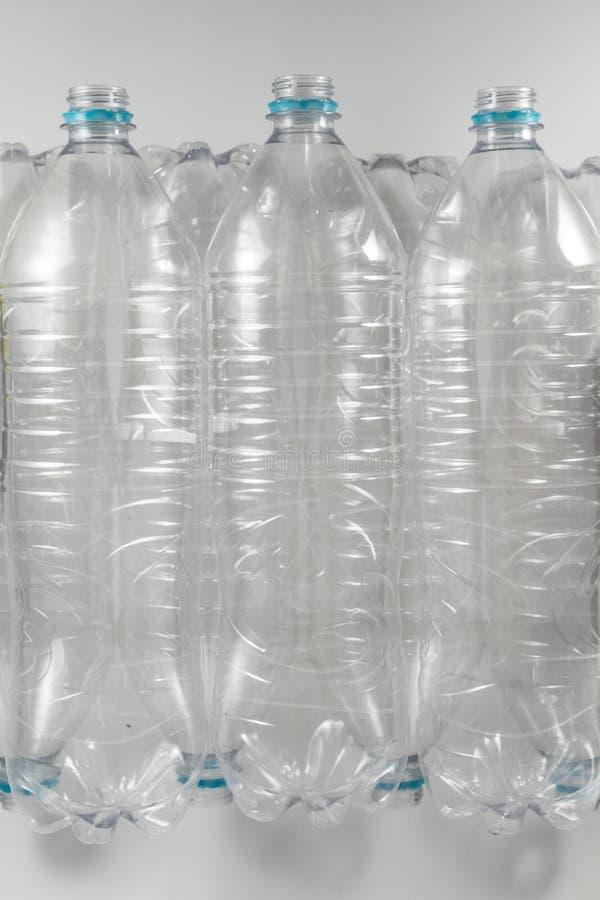 Вертикальный взгляд сверху пакета стоя бутылок литра и половины пустой минеральной воды без крышек как раз с стоковая фотография