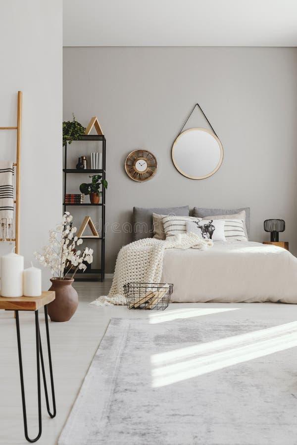 Вертикальный взгляд спальни ethno с большой удобной кроватью с бежевыми одеялом и подушками, реальным фото стоковая фотография rf