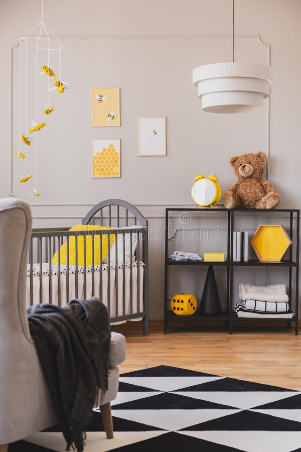 Вертикальный взгляд стильной серой и желтой спальни младенца стоковое изображение