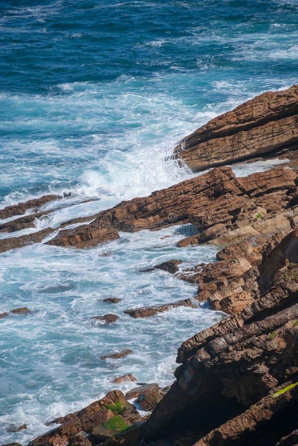 Вертикальный ландшафт с волнами против скалистого побережья стоковое изображение