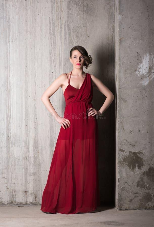 Вертикальный портрет красивой молодой женщины в длинном красном росте платья полностью стоковое изображение rf