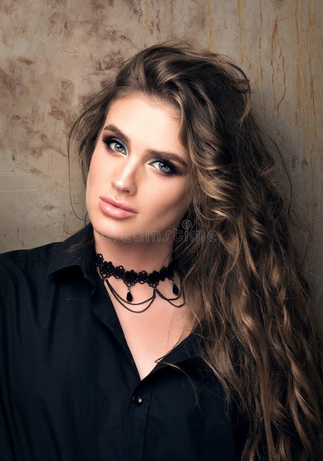 Вертикальный портрет крупного плана молодой красивой женщины в черной рубашке представляя перед стеной металла стоковые фото