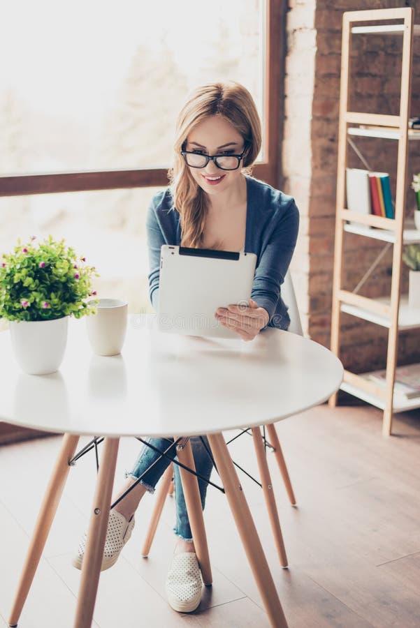 Вертикальный портрет милой женщины при испуская лучи улыбка сидя на стоковое изображение