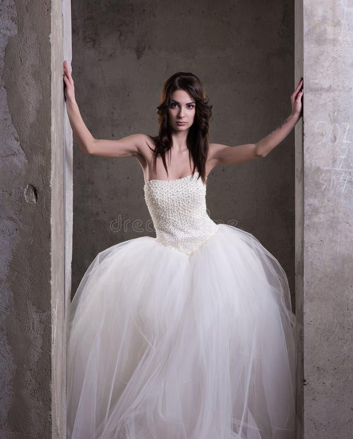 Вертикальный портрет молодой женщины в белом платье свадьбы с пушистой юбкой стоковая фотография rf