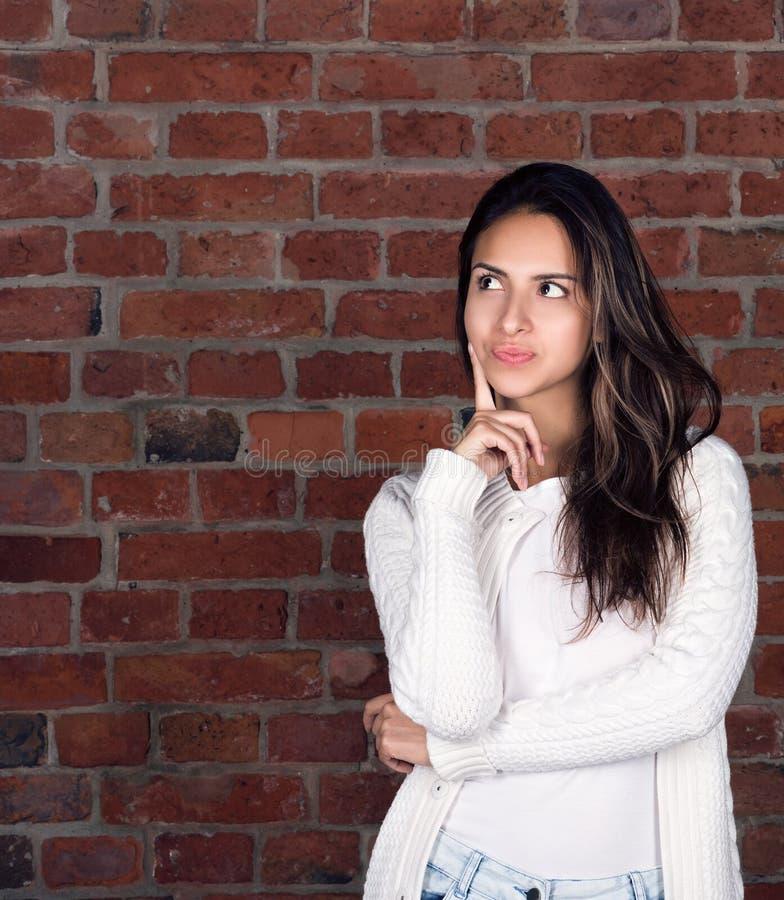 Вертикальный портрет привлекательной молодой женщины Думать о s стоковое изображение
