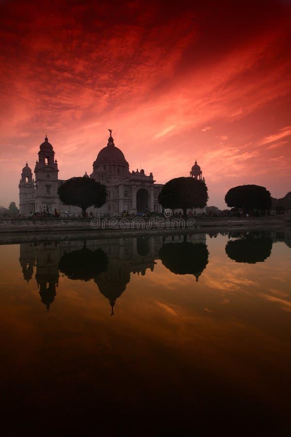 Вертикальный снимок мемориала Виктория в Калькутте, Индия, отразился в воде под красочным небом стоковая фотография rf