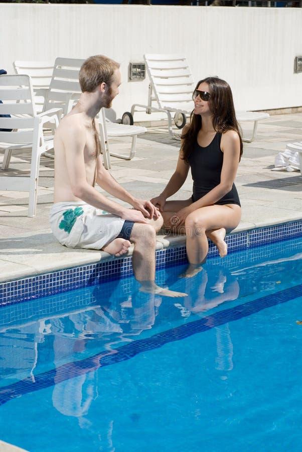 вертикаль poolside пар сидя стоковая фотография