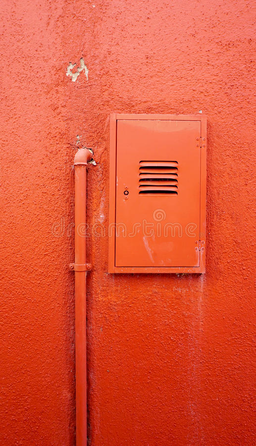 Вертикальная труба металла и электрическая коробка на оранжевой стене цвета стоковая фотография