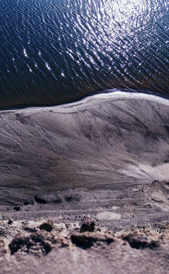 Вертикальный живой песок крутой на пляже океана стоковая фотография rf