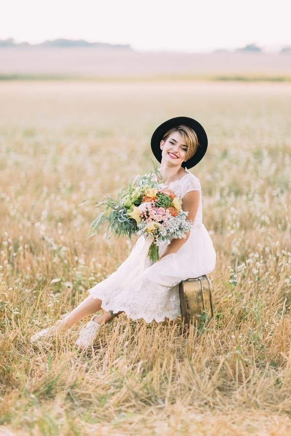 Вертикальный портрет усмехаясь невесты при красочный букет сидя на винтажном чемодане весной стоковые фотографии rf