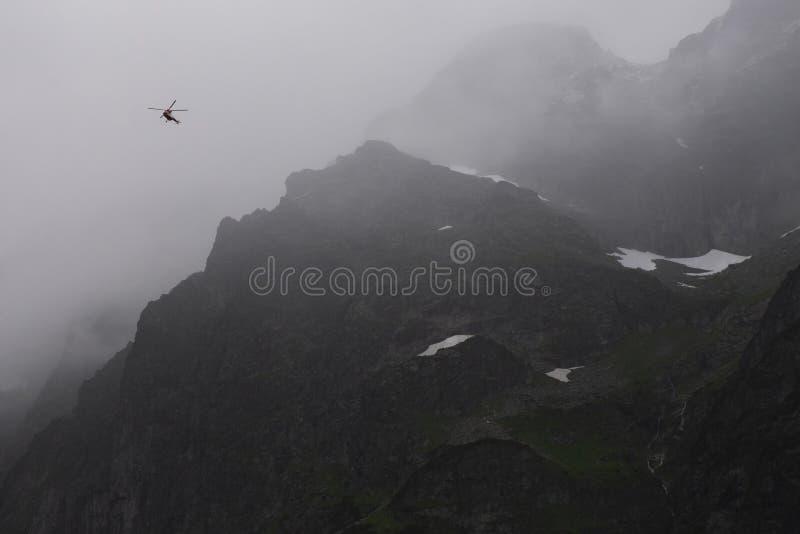 Вертолет в горах, густой туман спасения, Tatra стоковая фотография rf