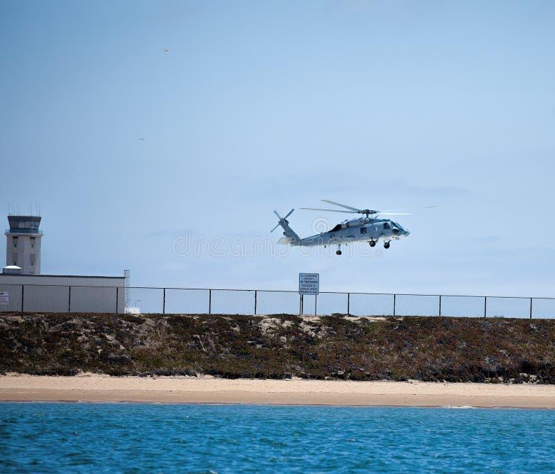 Вертолет Seahawk военно-морского флота проводит маневр около военноморского низкопробного Coronado стоковые фото