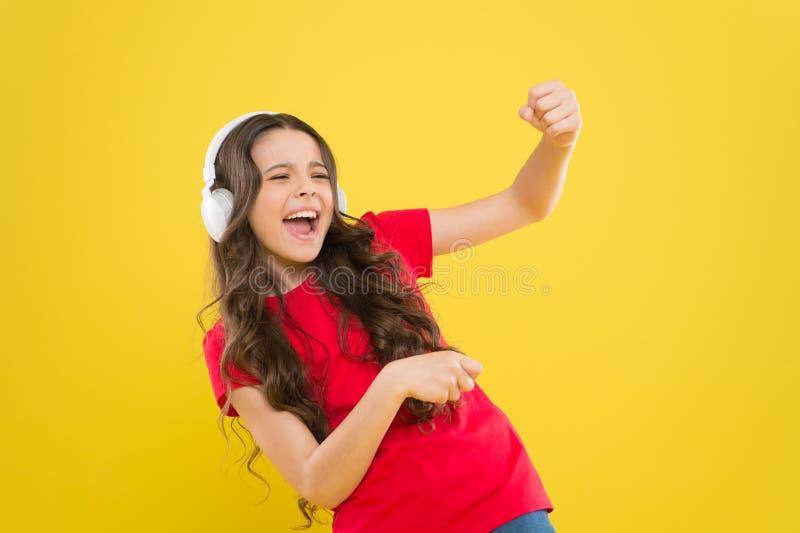 Верхние песни Ребенок предназначенный для подростков наслаждается музыкой играя в наушниках Маленькая девочка наслаждаясь любимой стоковое фото rf