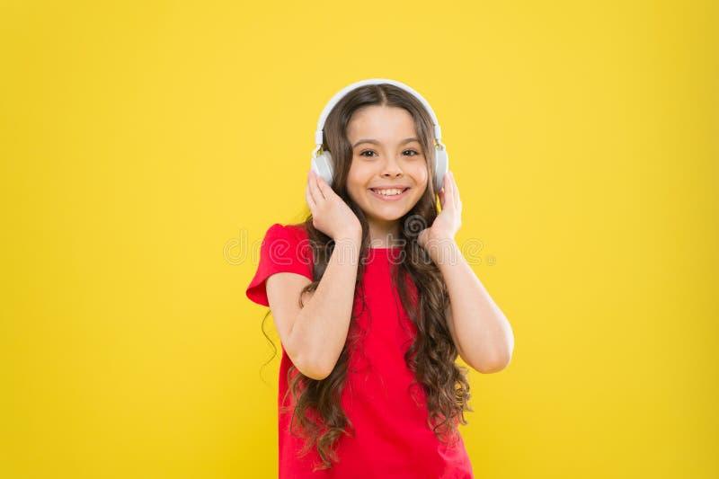 Верхние песни Ребенок предназначенный для подростков наслаждается музыкой играя в наушниках Маленькая девочка наслаждаясь любимой стоковые фото