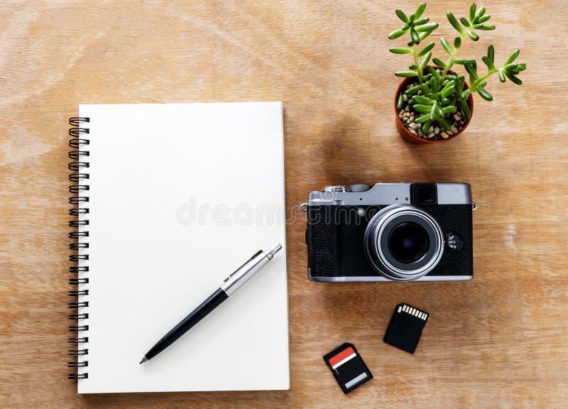 Верхний вид Столы с ноутбуками, ручками, камерами и картами памяти на деревянном фоне стоковые фото