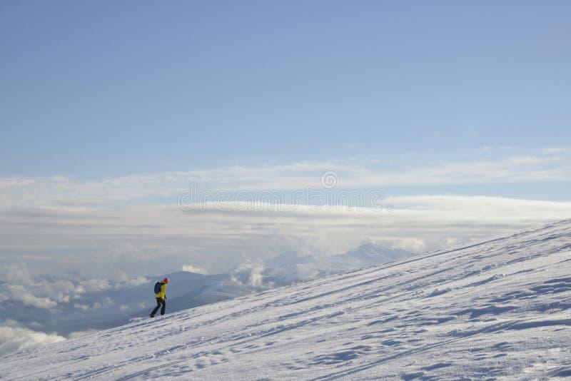 верхний мир Лыжник идет к верхней части горы над облаками стоковые фотографии rf