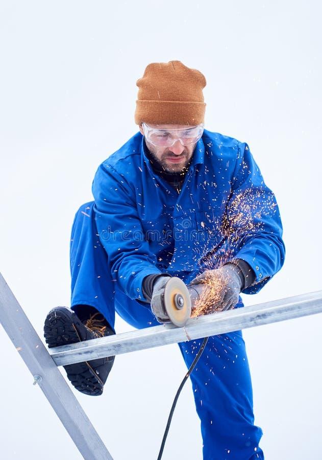Верхняя съемка мужского инструментального металла техника с режущим диском установить фотовольтайческие панели солнечных батарей стоковое фото rf