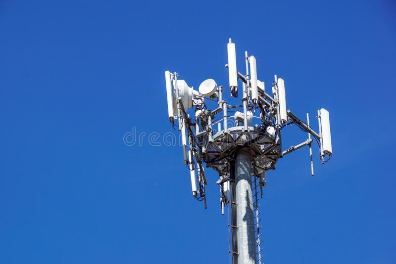 Верхняя часть башни связи сотового телефона с множественными антеннами против голубого неба стоковые изображения rf