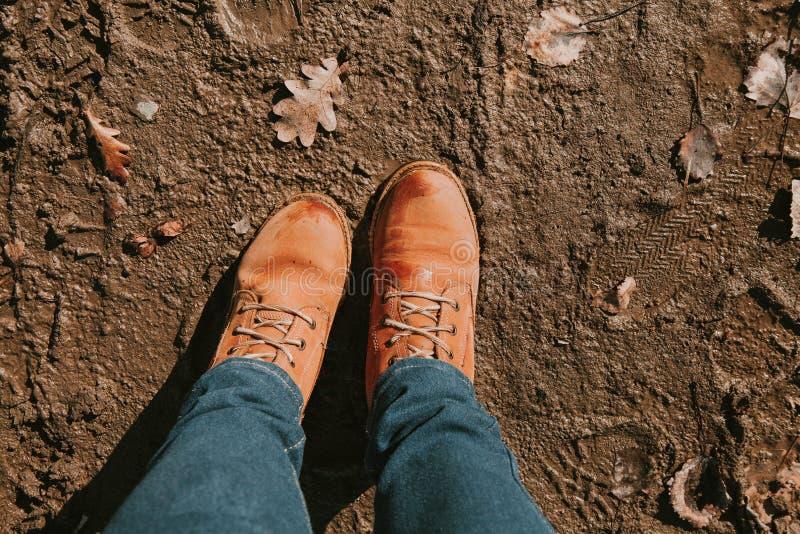 Верхняя часть вниз с грязных желтых зашнурованных ботинок в грязи, женщине в голубых джинсах стоковые изображения
