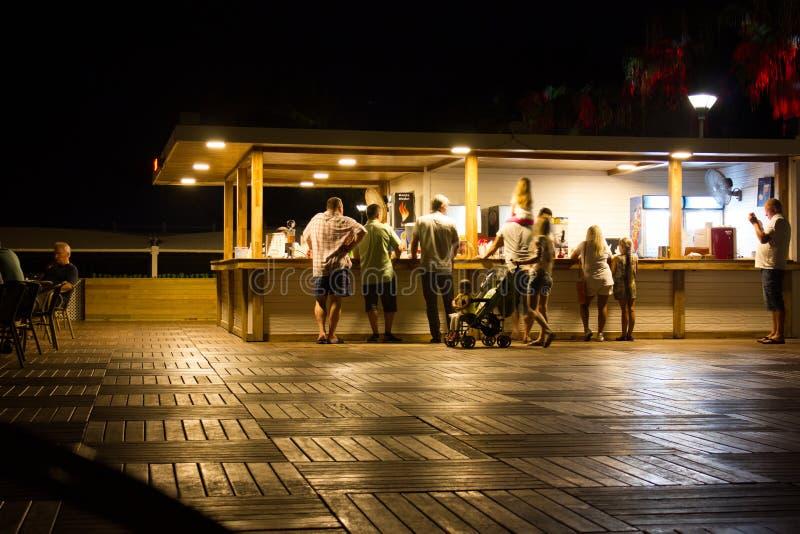 Верхняя часть деревянного стола над абстрактной предпосылкой нерезкости официальныйа обед людей на на открытом воздухе ресторане стоковая фотография rf