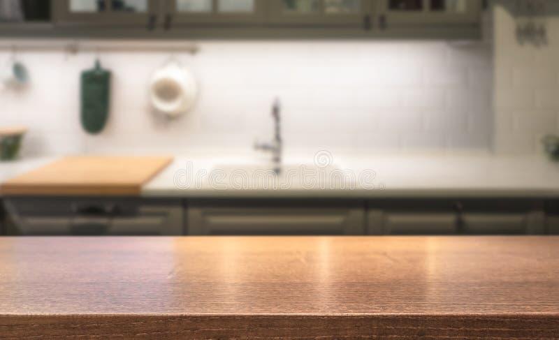 Верхняя часть деревянного стола на острове кухни перед запачканным домашним интерьером стоковые фотографии rf