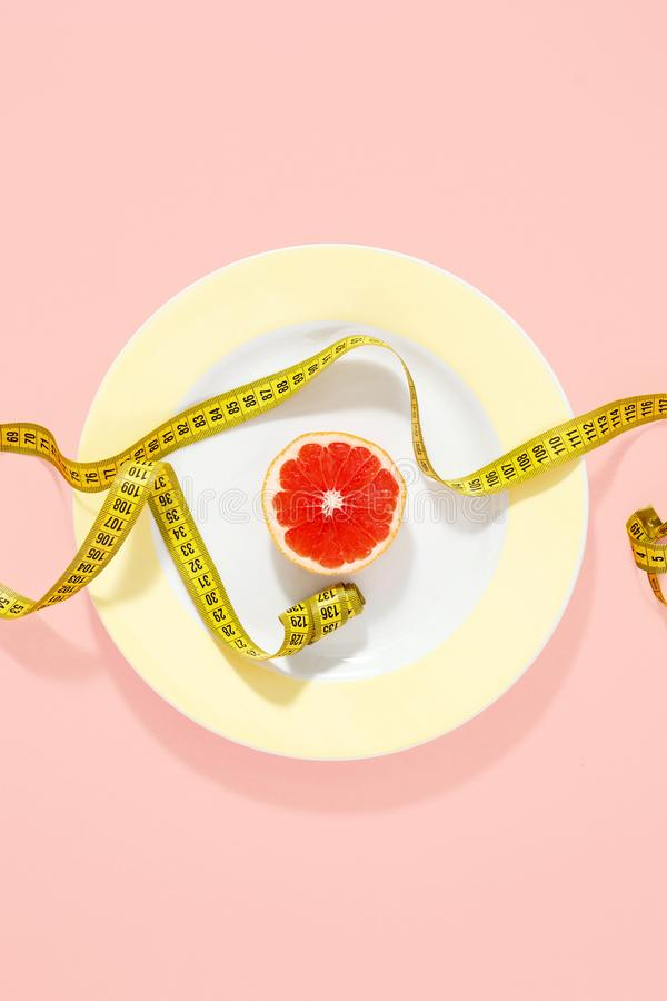 Верхняя часть предпосылки пинка грейпфрута ленты желтой плиты измеряя половинная стоковые фото