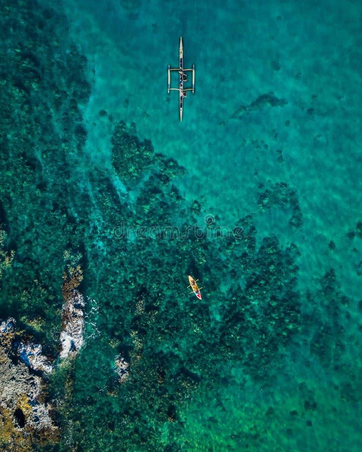 Верхняя часть трутня вниз с взгляда человека сплавляясь на каяке в ясной голубой воде teal стоковые изображения rf