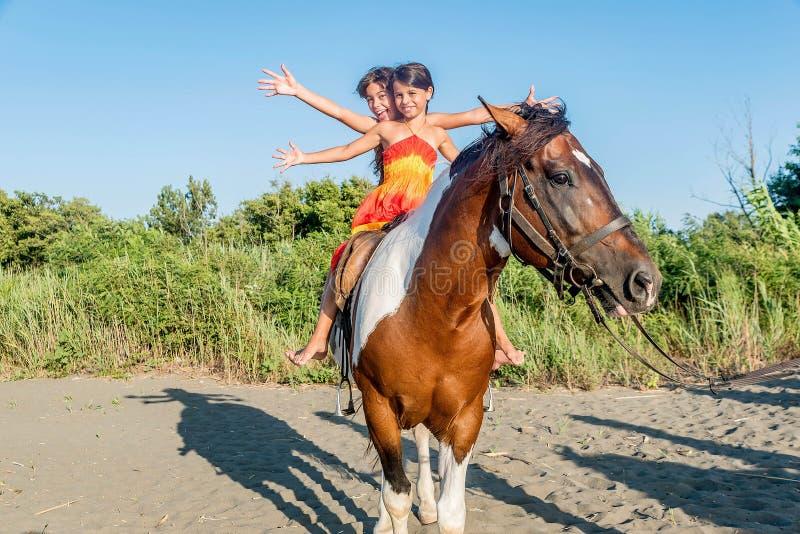Верховая лошадь 2 маленьких девочек в лете в Ada Bojana, Monte стоковые фотографии rf
