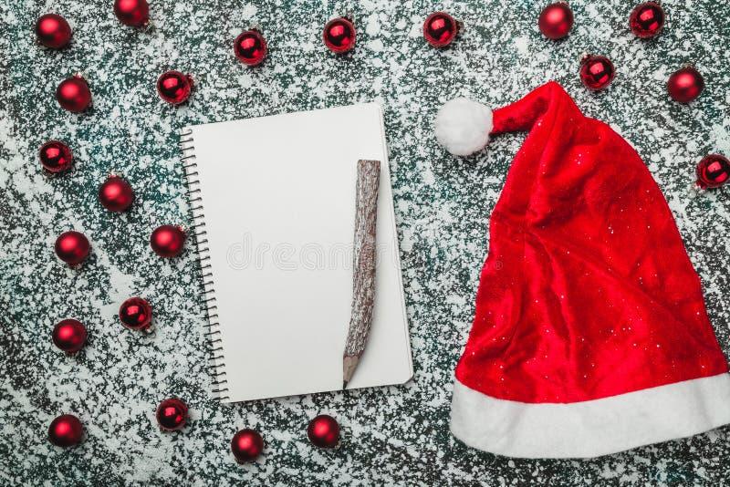 Верхушка, верхняя часть, осматривает сверху блокнота, деревянной винтажной ручки, вечнозеленых красных игрушек, шляпы Санты на се стоковое фото rf