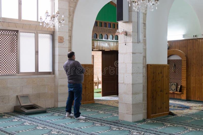 Веря мусульманин молит в белой мечети - al-Abiad в старом городе Назарета в Израиле стоковые фотографии rf