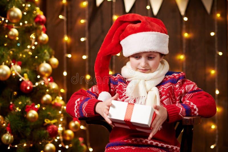 Веселая девушка-санта с подарочной коробкой, сидящая в помещении, рядом с декорированным xmas деревом с огнями, одетая в красный  стоковое изображение