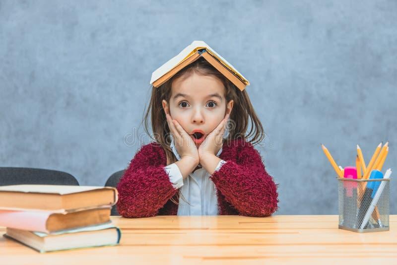 Веселая девушка, сидящая и держащая книгу над головой на сером фоне Во время этой школы девушка открыла рот стоковая фотография