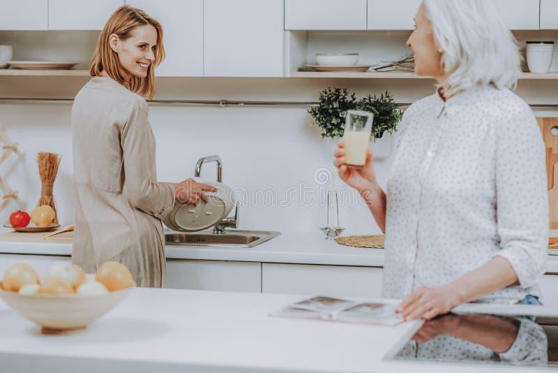 Веселая женщина моет блюда и разговаривает с матерью стоковые изображения