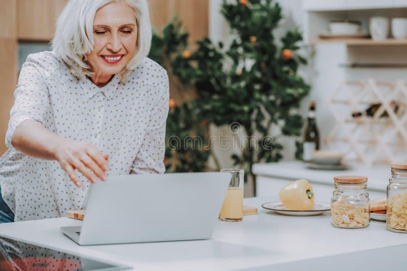 Веселая зрелая женщина использует ноутбук подготавливая еду стоковое изображение rf