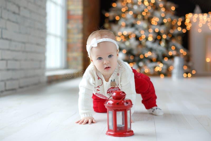 Веселая маленькая девочка играет одна, сидя на полу в комнате на фоне красивой елки. стоковое фото