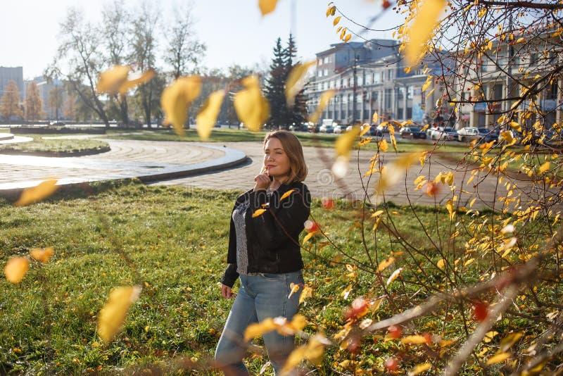 Веселая молодая женщина-извилистая, осени глядя на улицу Девочка наслаждается теплой солнечной погодой Она в синих джинсах и стоковое изображение