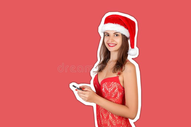 Веселая очаровательная молодая девушка в христмас-шляпе с помощью мобильного телефона в стиле коллажа red santa klus hat Magazine стоковые фото