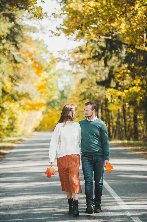 Веселая счастливая пара осенью в парке прогуливается по асфальтовой дороге и держит осенние листья в руках стоковое фото