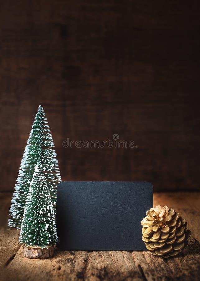 Веселое рождество и счастливый Новый Год на классн классном с деревом xmas и конус сосны золота на таблице grunge деревянной и те стоковые фотографии rf