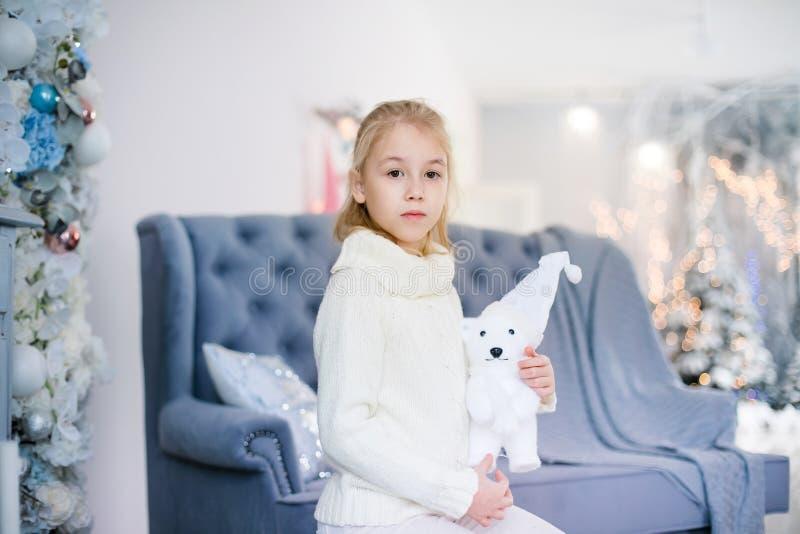 Веселое рождество и С Новым Годом!! Очаровывая маленькая белокурая девушка в белом теплом свитере с медведем игрушки сидя на голу стоковая фотография